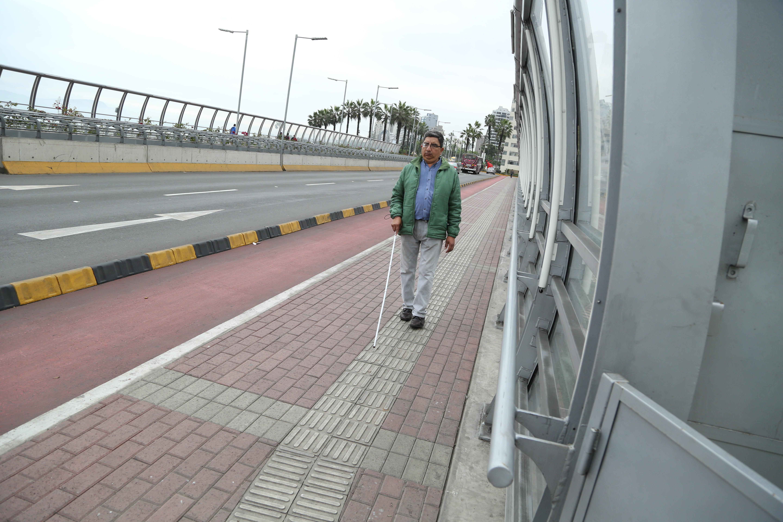 Persona caminando por vía podotáctil.
